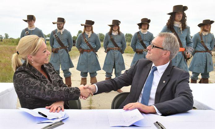 Minister Hennis-Plasschaert schudt de hand met Commissaris van de Koning Han Polman in 2014 (archief).