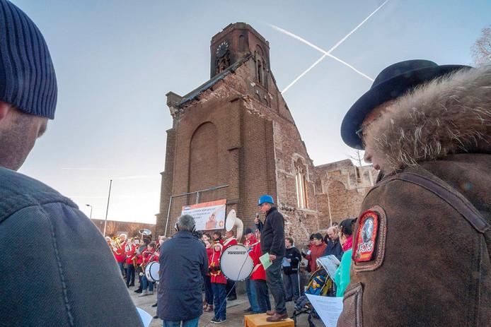 Onder leiding van ds Arie van der Maas (met blauwe veiligheidshelm) zingen de Hoekenezen het strijdlied: Laat de klok van Hoek weer luiden