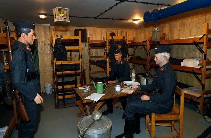 Het manschappenverblijf in de Biberbunker. Drie Duitse militairen zitten aan tafel met een fles Rutte-jenever.
