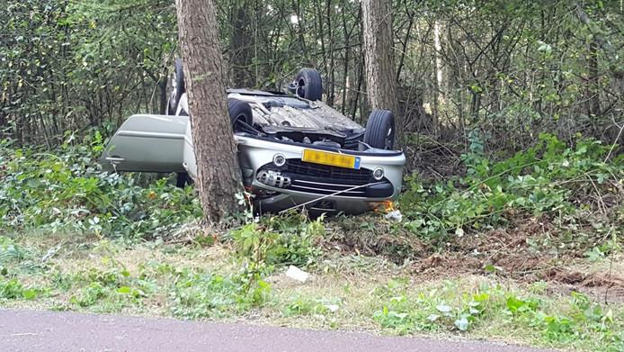 Auto op de kop tegen boom in Overasselt.