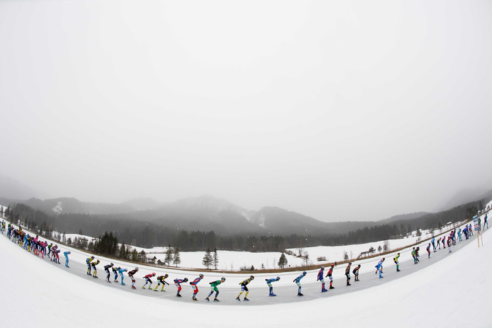 Marathonschaatspeloton in de sneeuw tijdens het open Nederlands Kampioenschap marathon op natuurijs.