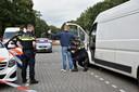 De politie doet onderzoek bij de witte bus met drugsvaten in Berkel-Enschot.