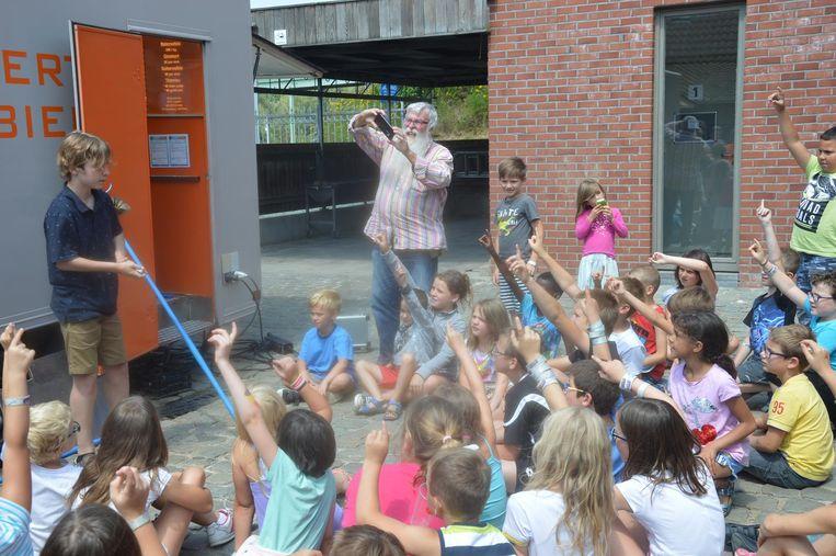 De kinderen zijn geboeid door de jonge goochelaar die gisteren langskwam.