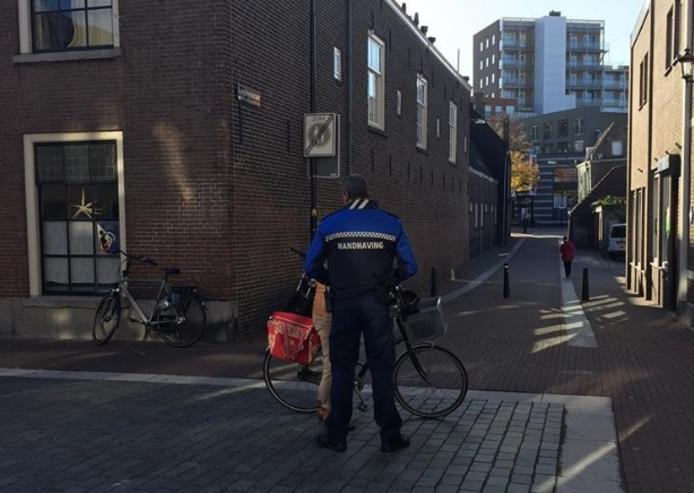 Dordtse handhavers delen een bekeuring uit aan een fietser, die tijdens winkeltijden door het centrum van Dordrecht fietste.