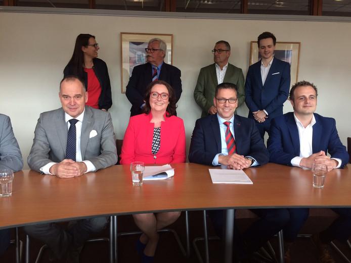 Het nieuwe college van Uden met op de achtergrond de fractievoorzitters van de vier samenwerkende partijen. Opvallend is dat de liberalen de sociale portefeuille van het PvdA overnemen. Maarten Prinssen (links) wordt daar verantwoordelijk voor.