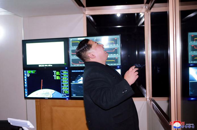Kim Jong-Un kijkt naar de lancering van de Hwasong 15 raket. Op een computerscherm is de hoogte van de raket t.o.v de aarde zichtbaar gemaakt.