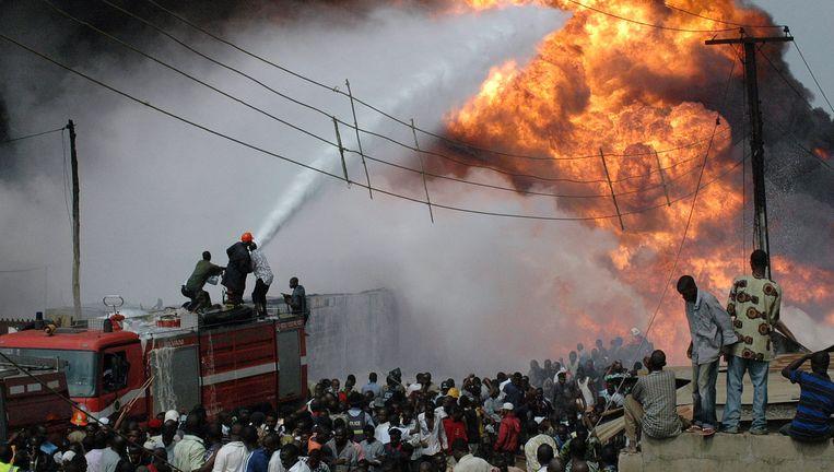 Brandweermannen proberen in mei 2008 in Lagos een brand te blussen nadat een oliebuis is geëxplodeerd. De oliesector is in Afrika verreweg de grootste melkkoe voor sluwe boekhouders. Beeld AFP