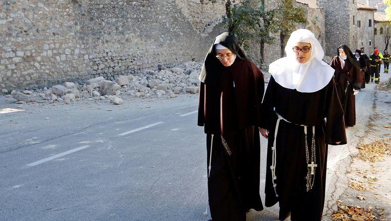 Nonnen lopen in Norcia langs een ingestorte muur. De aardbeving vond 6 kilometer van het stadje plaats. Beeld null