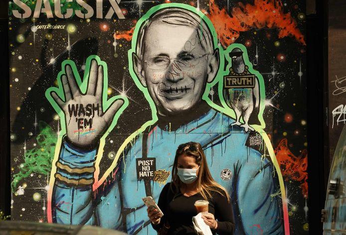Een vrouw loopt langs een muurschildering waarop Anthony Fauci afgebeeld is in Manhattan.