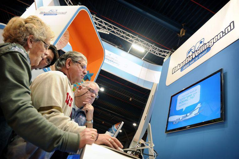 Mensen op een vakantiebeurs bekijken een internetveiling van vakantieveilingen.nl. Beeld null