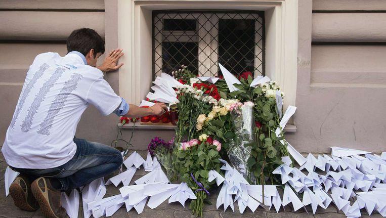 Een man plaatst een kaars bij de Nederlandse ambassade in Moskou, een jaar na de ramp met MH17. Beeld anp
