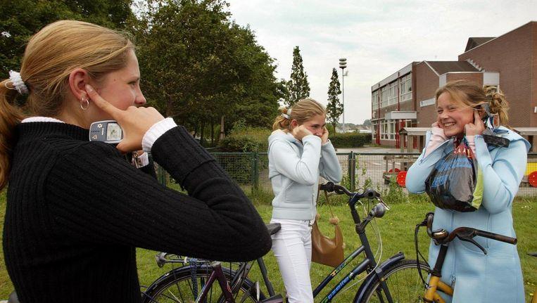 Scholieren in Hoek van Holland houden hun oren dicht voor de loeiende sirene. Beeld null