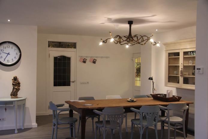 Een deel van de woonkamer waar de mensen aan een grote tafel kunnen zitten.