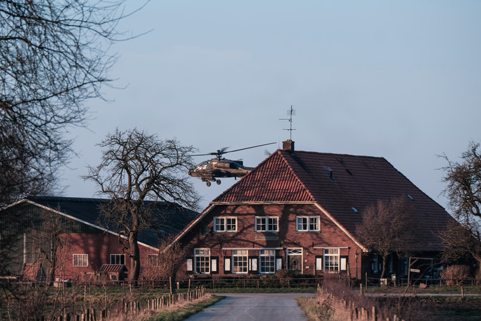 Een Apache-heli van Defensie doemt op van achter een boerderij in de Fraterwaard in Doesburg.