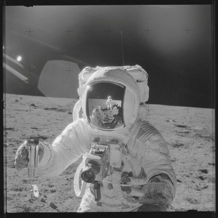 Alan L. Bean met in zijn vizier mede-maanreiziger Pete Conrad, die de foto nam. Bean houdt speciale cilinder vast, waarin maanmateriaal verzameld moet worden.