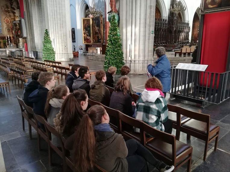 Leerlingen luisteren met veel aandacht naar één van de gidsen