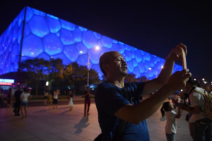 Een toerist neemt een foto voor de Watercube. In 2022 zal hier de curlingcompetitie plaatsvinden voor de Olympische winterspelen.
