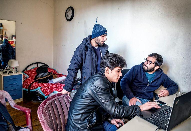 Syrische vluchtelingen Akram Saud (staand), Abdel-Qader Zalhka (links) en Fouad Hallak (rechts) bekijken het nieuws uit Syrië op een laptop. Beeld Raymond Rutting/de Volkskrant