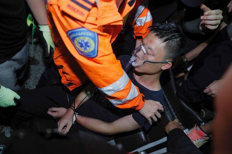 Een hulpverlener helpt een man die door de betogers is vastgebonden.