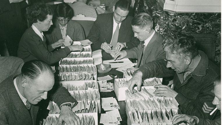 Na de bevrijding: zoeken in kaartenbakken naar gegevens over vermisten. Beeld Nederlandse Rode Kruis, Oorlogsarchief