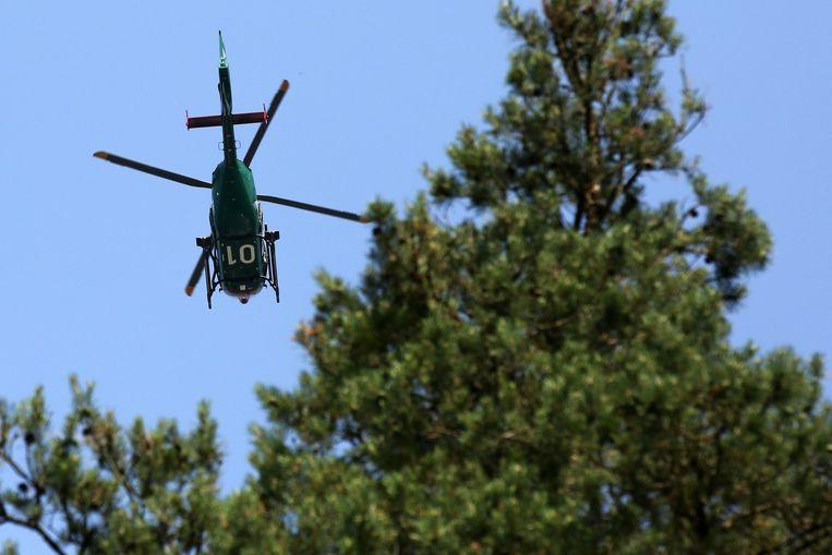 Een politiehelikopter vliegt over een bos in  de Duitse deelstaat Mecklenburg-Vorpommern heen.