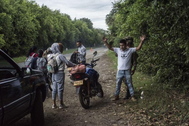Soldaten van het Colombiaanse leger controleren reizigers op drugs en wapens op een snelweg in de buurt van Corinto. Beeld Stephen Ferry