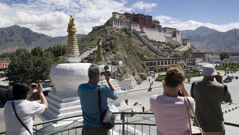 Toeristen fotograferen het Potala Paleis, voormalige residentie van de Dala Lama. Beeld EPA
