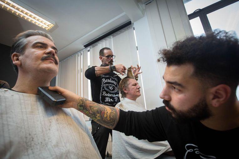 De barbiers nemen de haren en baard van enkele dak- en thuislozen onder handen.
