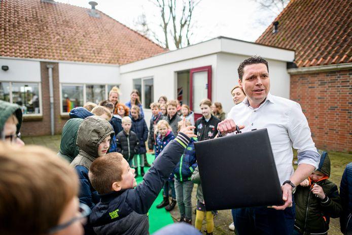 Wethouder Wim Meulenkamp geeft samen met leerling Tim Wiggers (blauw/oranje jas) het startsein voor de eco-school. Schooldirecteur Dorien Klein Teeselink (in blauwe jurk).