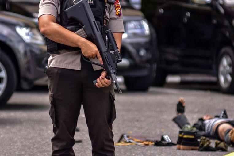 Een agent houdt de wacht naast het lichaam van een van de daders.