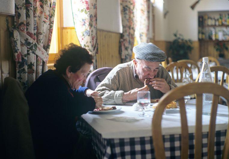 Een ouder echtpaar eet lunch met veel vlees in een Spaans eettentje.  Beeld Marcel Malherbe