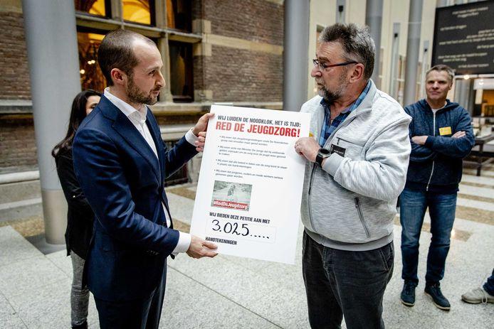 Werknemers van de jeugdzorg-instelling Hoenderloo Groep overhandigen in de Tweede Kamer een petitie aan Maarten Hijink (SP, links op de foto) namens de vaste commissie voor Volksgezondheid