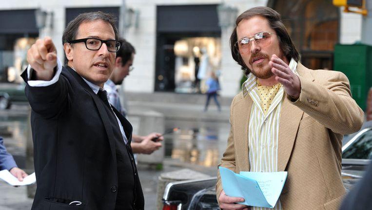 Hoofdrolspeler Christian Bale met schrijver David O'Russell (L) tijdens de opnames van American Hustle. Beeld getty
