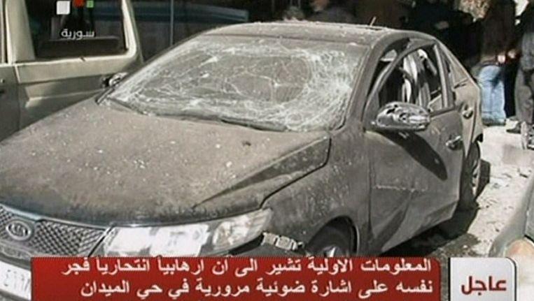 Beelden van de Syrische staatstelevisie laten vandaag een auto zien die beschadigd raakte door de explosie. Beeld afp