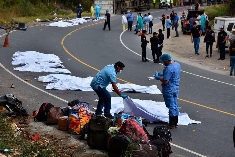 De lichamen van de overledenen worden door forensische medewerkers op de weg gelegd.