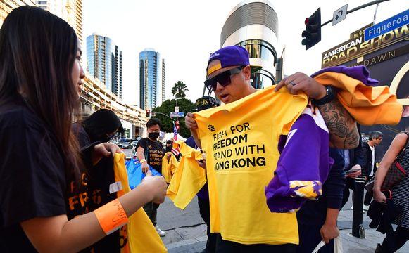 Bij de openingswedstrijden verdeelden aanhangers van de prodemocratiebeweging in Hongkong T-shirts in steun van de protesten, hier aan het Staples Center in Los Angeles.