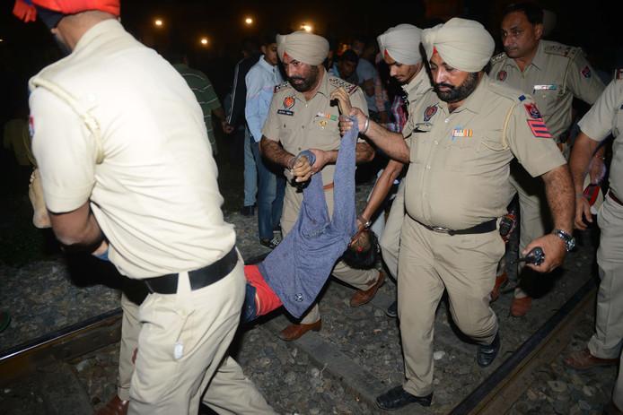 Indiase agenten halen het lichaam van een slachtoffer van de rails.