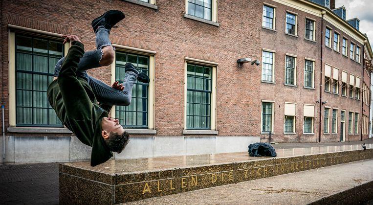 Een jongen maakt een salto voor de grondwetbank, het monument voor de Grondwet aan de Hofplaats in Den Haag, waarop de tekst van artikel 1 is aangebracht, dat begint met:  'Allen die zich in Nederland bevinden, worden in gelijke gevallen gelijk behandeld'.  Beeld Freek van den Bergh / de Volkskrant