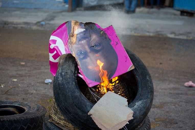 Een brandende poster met een afbeelding van Jovenel Moise, bij een demonstratie georganiseerd door aanhangers van diens rivaal Maryse Narcisse. Beeld AP