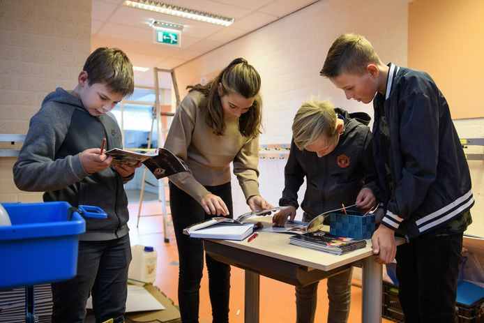 Oud-leerlingen bekijken de schoolgids en schrijven hun naam in het gastenboek.