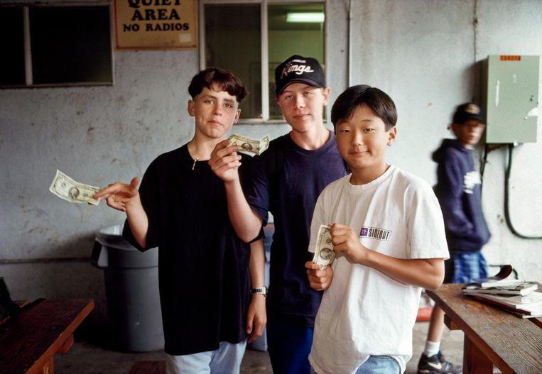 Leerlingen van de Crossroads School wapperen met 100-dollarbiljetten, Santa Monica, 1992. Beeld Lauren Greenfield/INSTITUTE