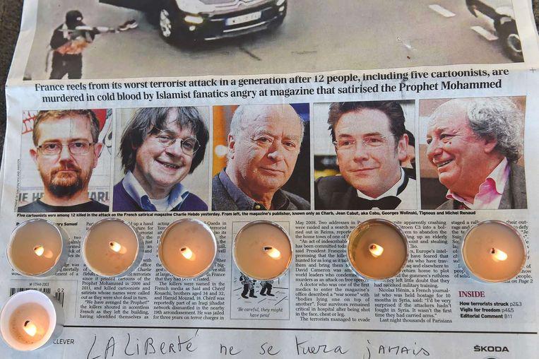 Bij een herdenking in Marseille zijn waxinelichtjes geplaatst op een krant met de afbeeldingen van de vermoorde redacteuren van Charlie Hebdo. Beeld afp